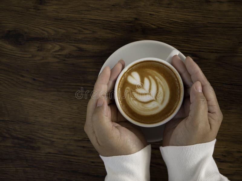 与美好的拿铁艺术的咖啡拿铁在手边 免版税库存图片