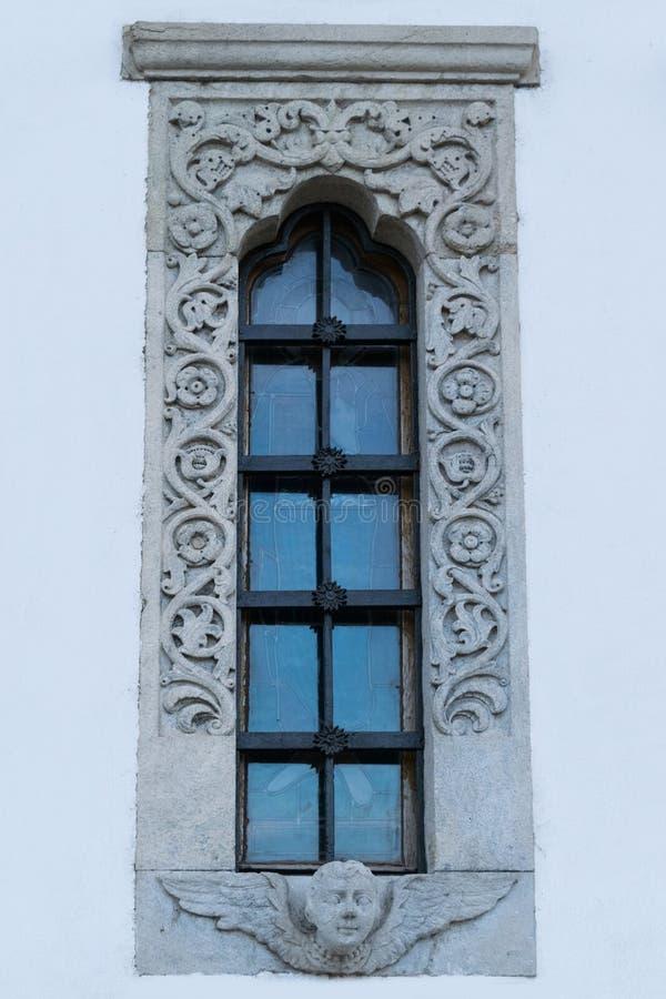与美好的精心制作的石被雕刻的框架的教会窗口 免版税库存照片