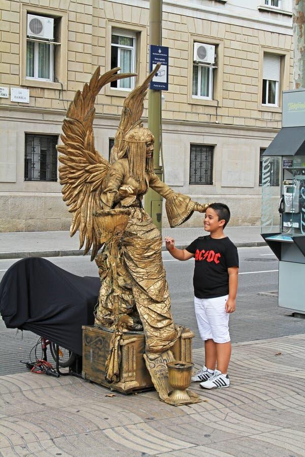 与翼和微笑的男孩的金黄被绘的生存雕象Ramblas街道的在巴塞罗那 图库摄影