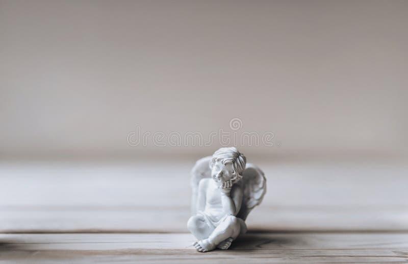 与翼的一名小丘比特在一个沉思姿势坐 圆形露天剧场 丘比特 免版税图库摄影