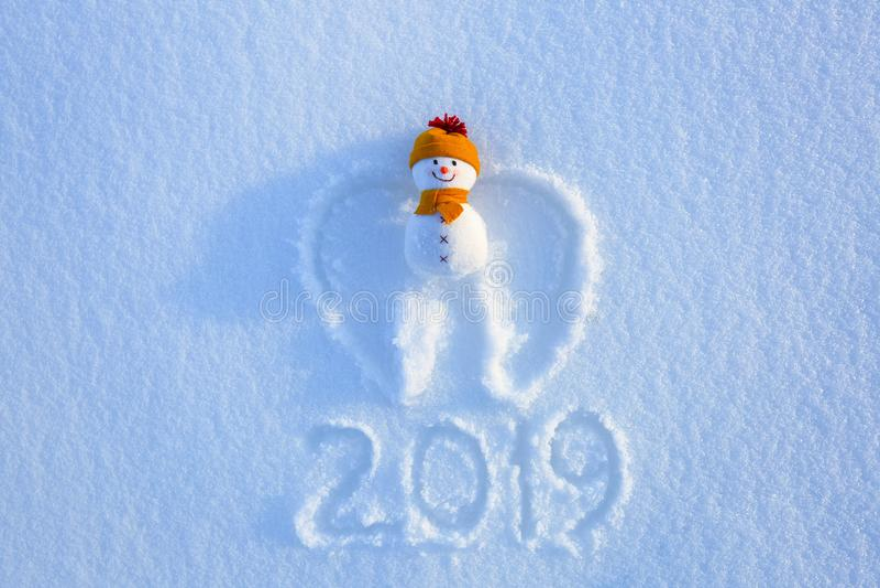 与翼的雪天使在黄色帽子和围巾在雪放置 写2019年 新年好 库存图片