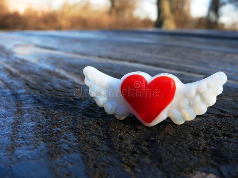 与翼磁铁的红色心脏在野餐桌上 免版税库存图片