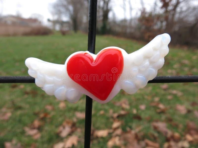 与翼磁铁的红色心脏在金属篱芭围绕 库存照片
