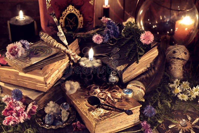 与老不可思议的书和礼节对象的静物画在神秘的烛光 图库摄影