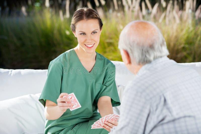 与老人的微笑的女性护士纸牌 免版税库存照片