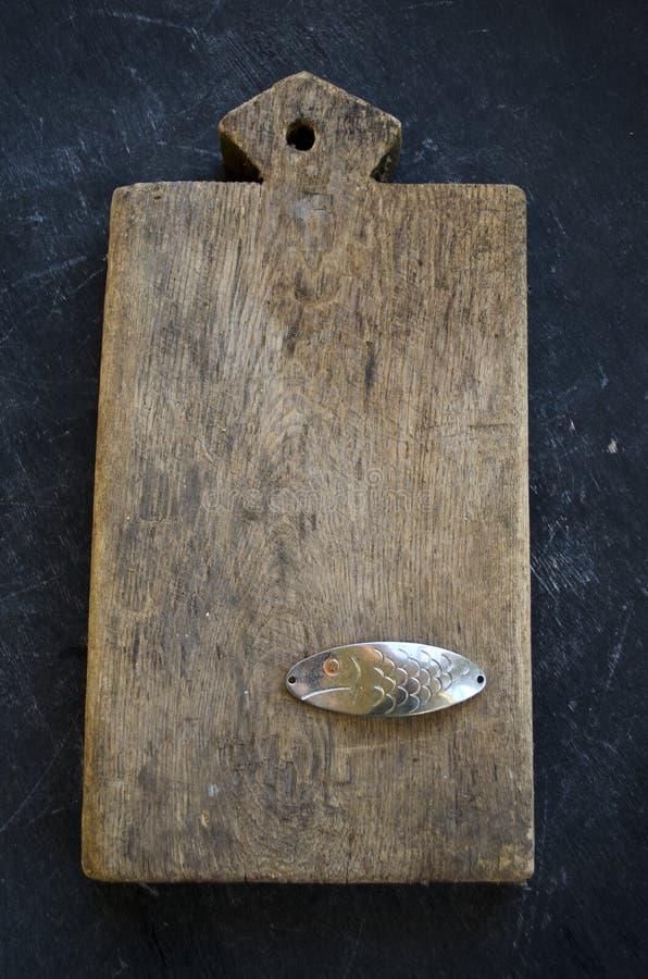 与老厨房切板和金属匙子诱饵的静物画钓鱼 免版税库存图片