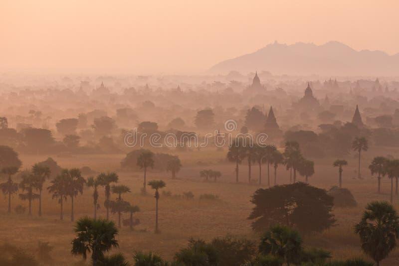 与老古庙和棕榈树剪影的橙色神秘的日出风景视图在黎明雾从气球 免版税库存照片