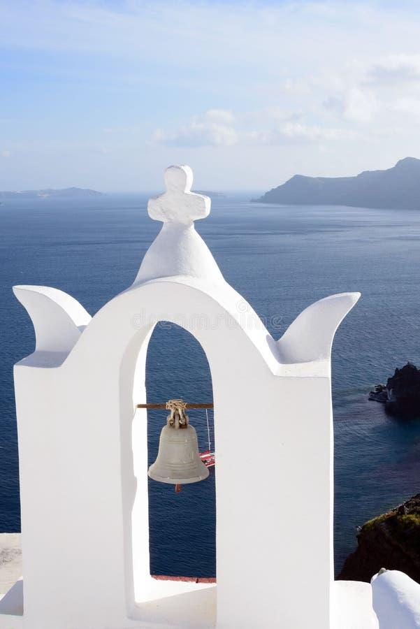 与老响铃的白色钟楼 美好的海视图在Oia在圣托里尼,希腊海岛上的  免版税库存照片