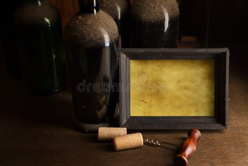 与老尘土酒瓶的静物画 免版税库存照片