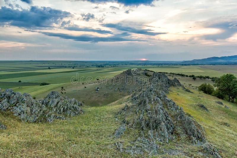 与老岩石、树、绿色领域和多云天空的美好的农村风景 免版税库存图片