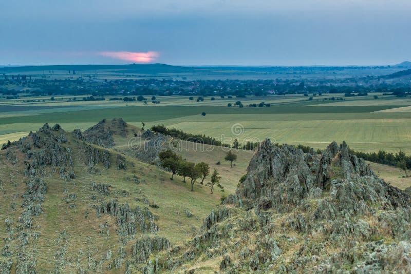 与老岩石、树、绿色领域和多云天空的美好的农村风景 免版税图库摄影