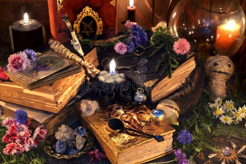 与老巫婆书、古色古香的灯、黑蜡烛、伏都教玩偶和仪式的静物画反对 库存图片
