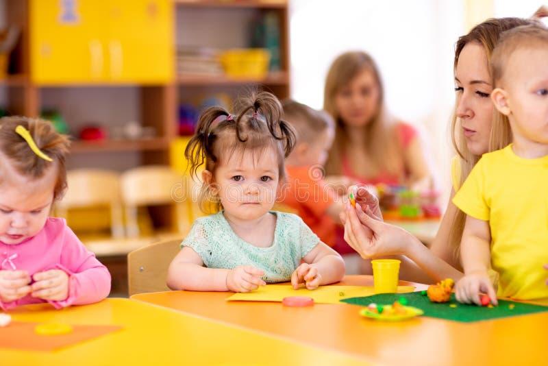 与老师模子的Cchildren从在桌上的彩色塑泥在托儿所 图库摄影