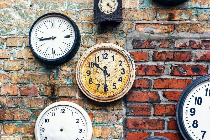 与老手表的难看的东西背景 背景概念查出的目的程序时间白色 在墙壁上的减速火箭的时钟 在年迈的红砖墙壁背景的老古色古香的时钟 免版税库存图片