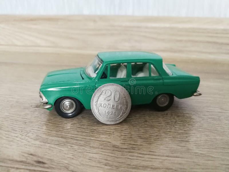 与老硬币比较的汽车式样玩具 免版税库存照片