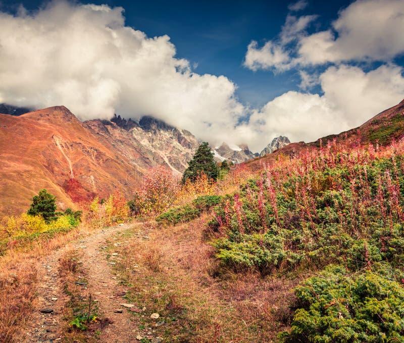 与老肮脏的路的晴朗的秋天lanscape在高加索山脉 免版税库存图片