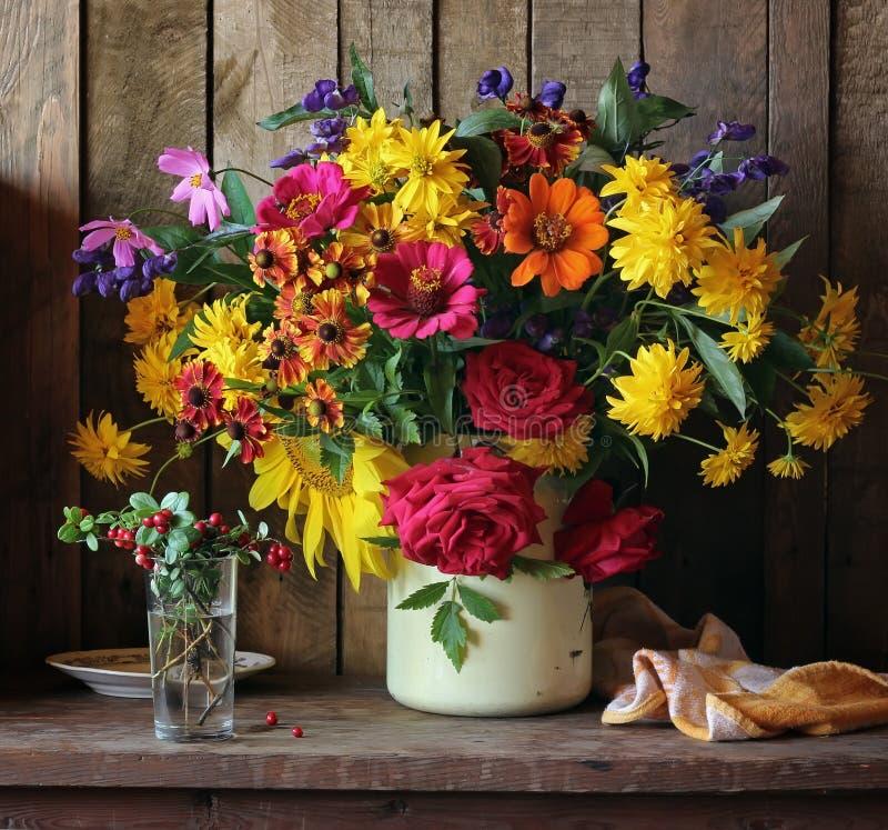 与耕种的花和越橘花束的静物画  图库摄影