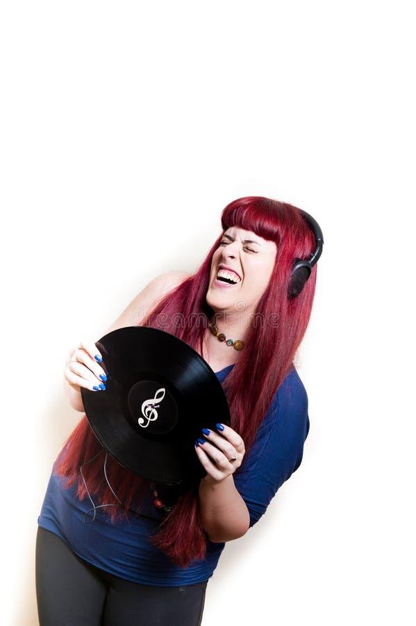 与耳机和唱片的年轻俏丽的妇女跳舞 免版税库存图片