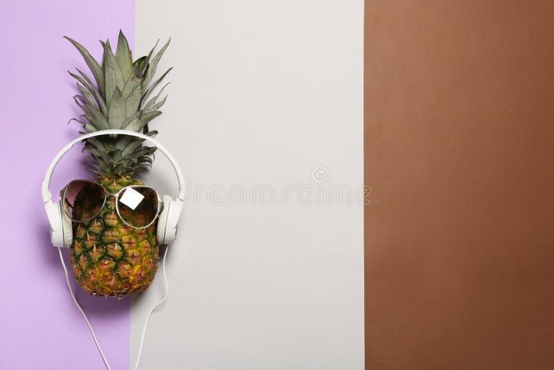 与耳机和太阳镜的滑稽的菠萝在颜色背景,顶视图 免版税库存图片