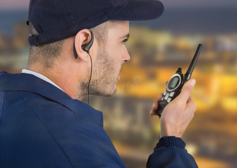 与耳机和携带无线电话的治安警卫有被弄脏的夜背景 免版税库存图片