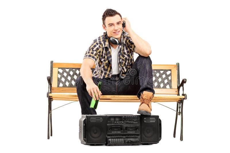 年轻与耳机和饮用的啤酒的人听的音乐 免版税库存照片