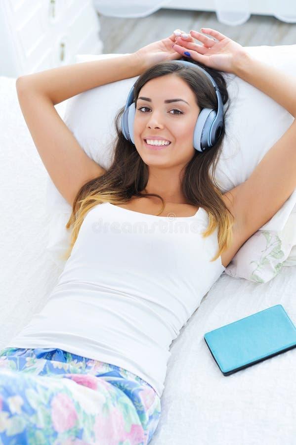 与耳机和e书的美丽的妇女画象 免版税库存照片