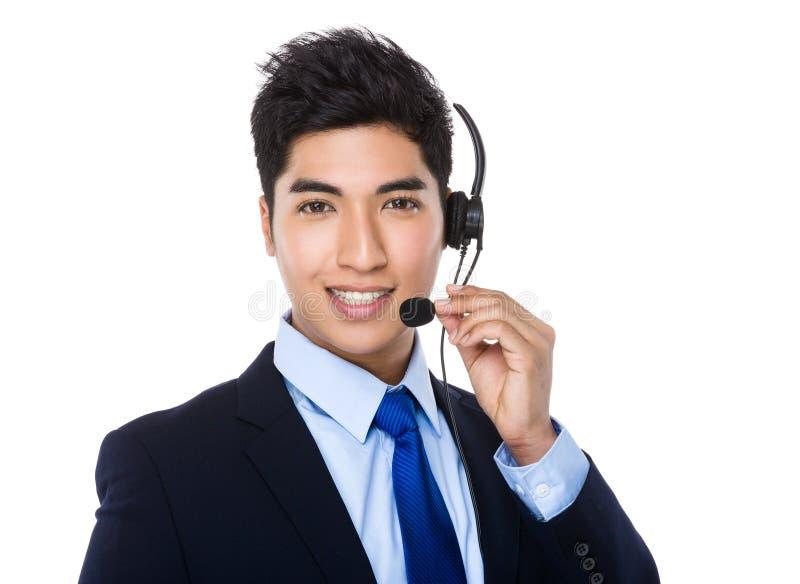 与耳机的亚洲年轻商人 免版税库存图片