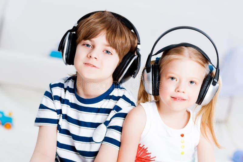 与耳机的兄弟和姐妹听的音乐 免版税库存照片