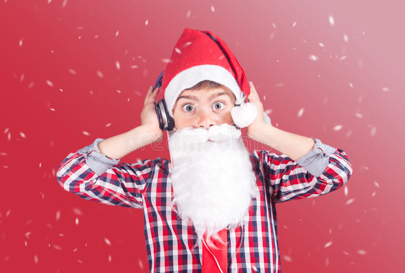 与耳机的可爱的滑稽的小的圣诞老人 十字架被处理的图象 图库摄影