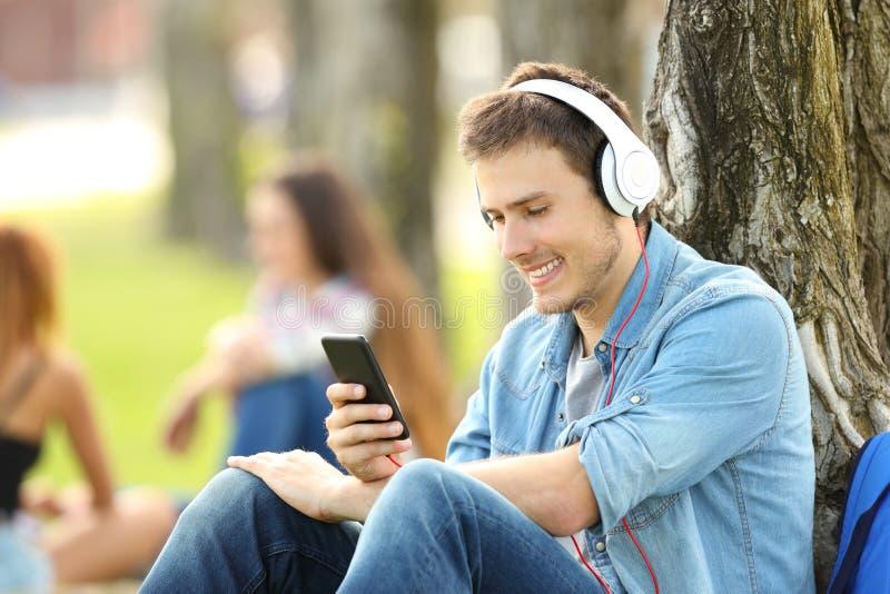 与耳机的学生听的音乐在公园 库存照片