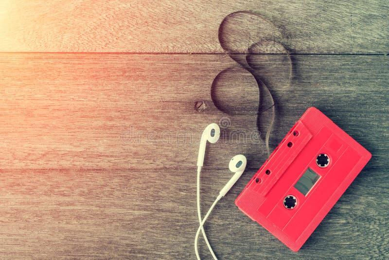 与耳机的红色盒式磁带在木桌 顶视图 浸泡 库存照片