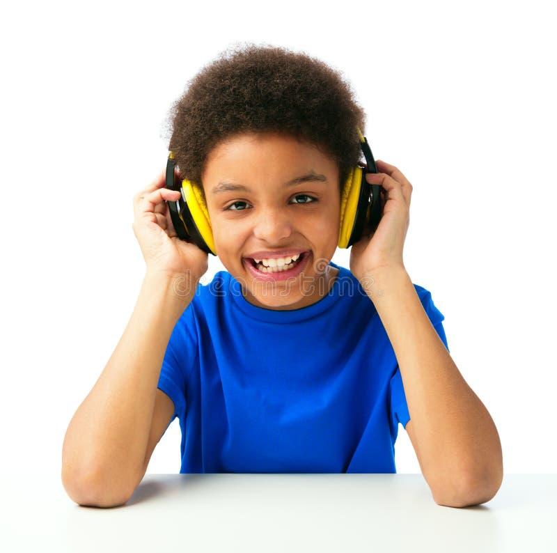 与耳机的非裔美国人的男生听的音乐 免版税库存照片