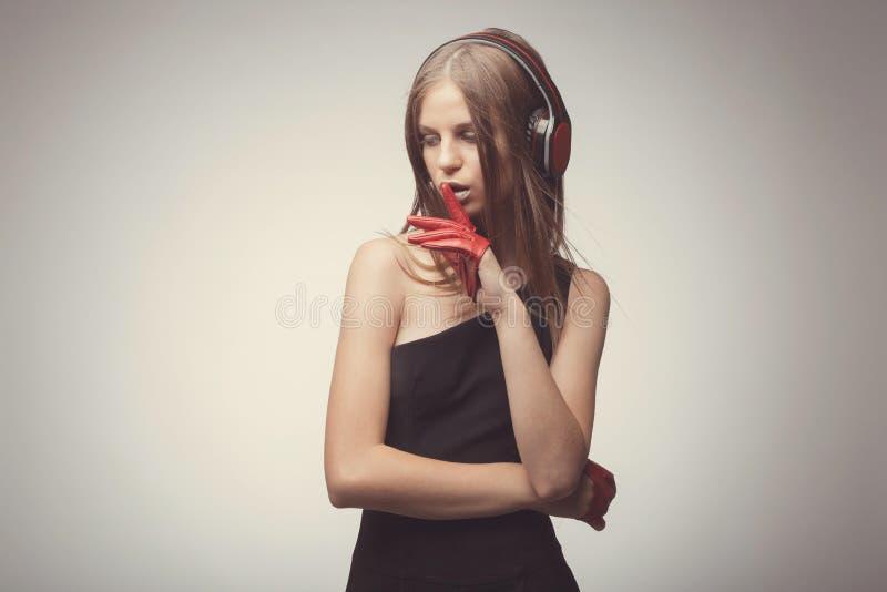与耳机,佩带的红色手套的时尚俏丽的女孩听的音乐,采取与歌曲的乐趣,并且要求大家关闭, 库存图片