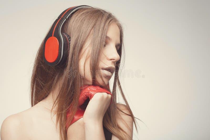 与耳机,佩带的红色手套的时尚俏丽的女孩听的音乐,采取与歌曲的乐趣 生活方式妇女概念 免版税库存照片