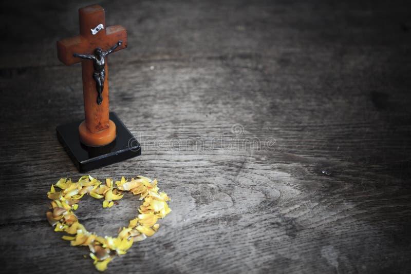 与耶稣的美好的老从叶子的十字架和心脏在老木地板上 免版税库存照片