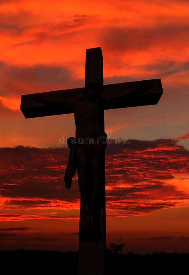 与耶稣的身体的水泥与实物大小一样的十字架作为太阳落山的 图库摄影