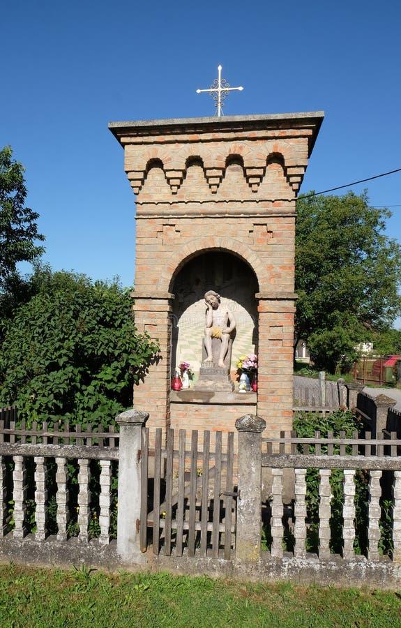 与耶稣雕象的宽容路边寺庙基督受难日的在Scitarjevo,克罗地亚 库存图片