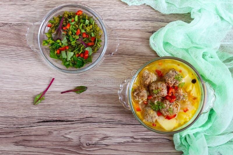 与肉丸和菜的米汤在一个透明玻璃碗 库存照片