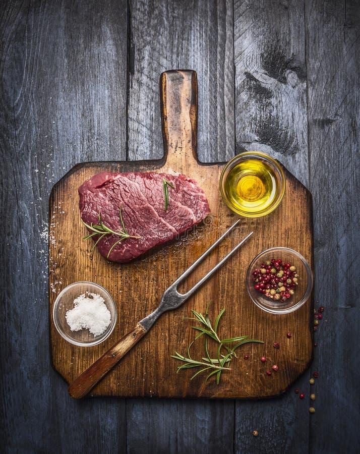 与肉叉子的未加工的新鲜的使有大理石花纹的在土气切板的牛排和调味料在蓝色木背景 免版税库存照片