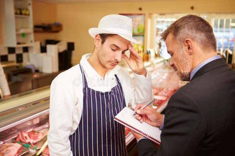 与肉店店主的银行经理会议  库存照片