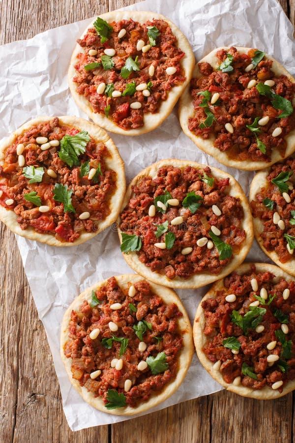 与肉末、蕃茄、葱、香料和松果特写镜头的阿拉伯微型比萨 垂直的顶视图 库存照片