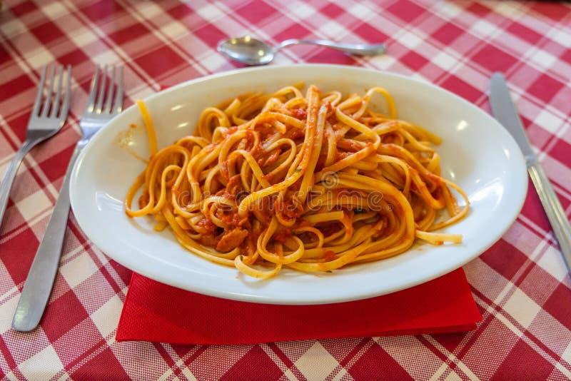 与肉末和西红柿酱混合的意粉在餐馆 图库摄影