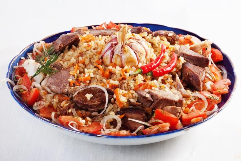 与肉饭乌兹别克人盘的盘,大蒜,葱,红萝卜,蕃茄,牛肉,肉,大,隔绝在白色背景 库存照片
