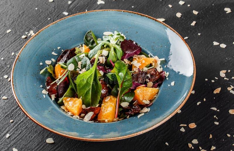 与肝脏、芝麻菜、桔子、菠菜和杏仁的沙拉在黑暗的石表面的板材 r r 库存图片