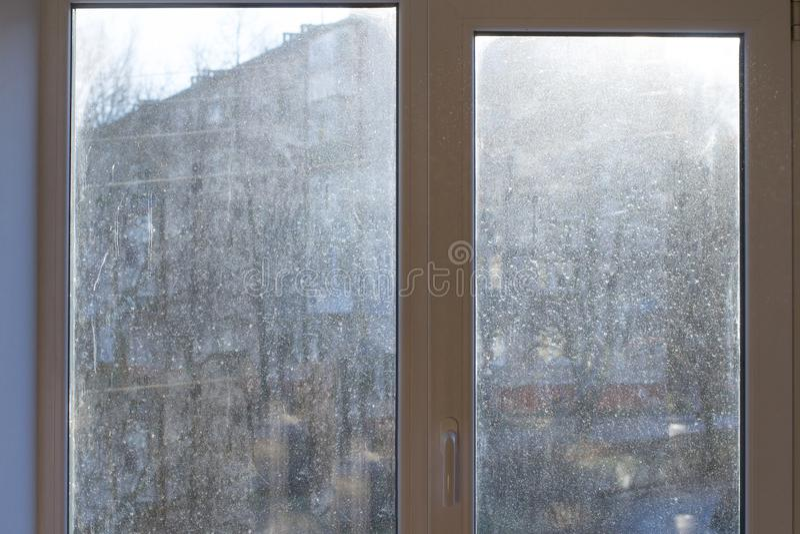 与肮脏和多灰尘的玻璃的窗口在白天 免版税库存照片