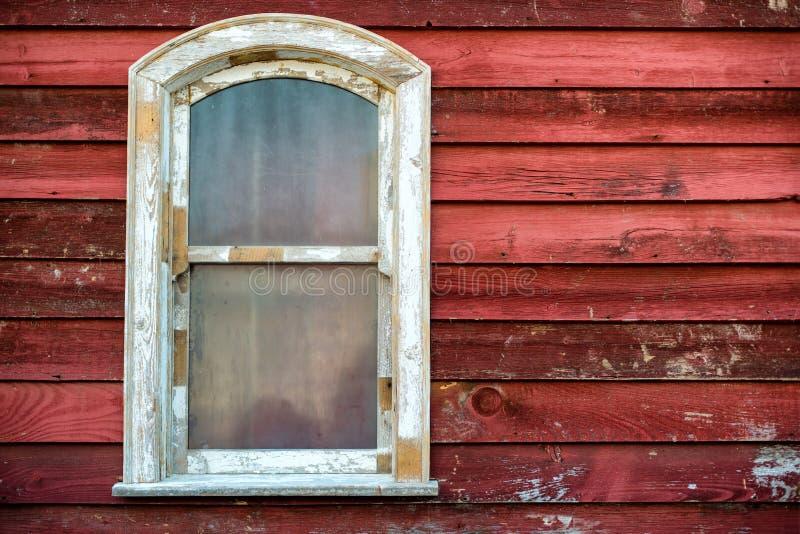 与肮脏的玻璃的老寡妇框架在红色木房子墙壁上 免版税库存照片