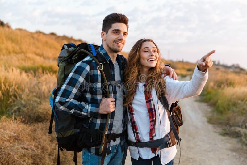 与背包的愉快的年轻爱恋的夫妇外部在自由供选择假期野营 免版税库存图片