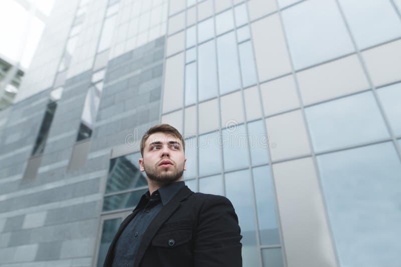与胡子和一套黑衣服的商人在现代轻的建筑学背景站立  库存照片