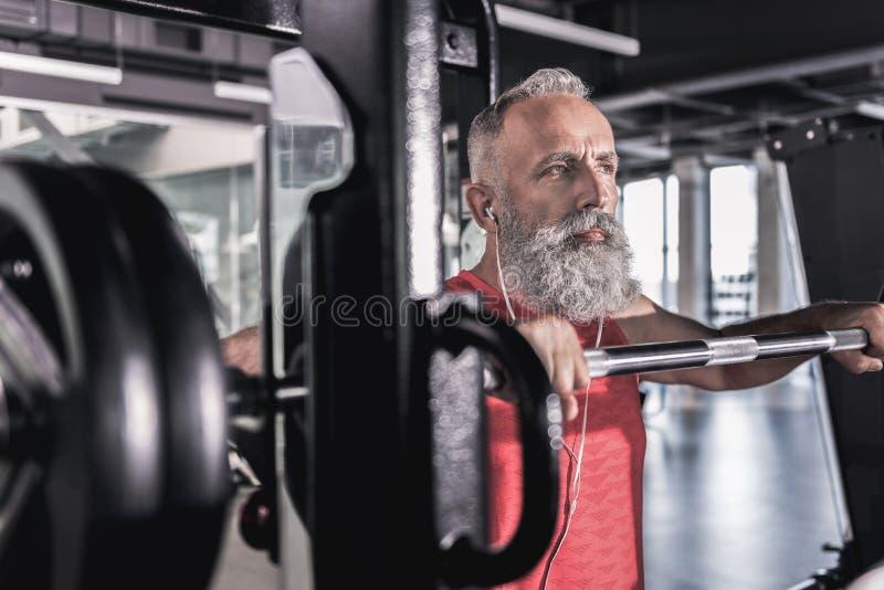 与胡子的沉思严肃的男性在运动中心的享受锻炼 免版税库存图片