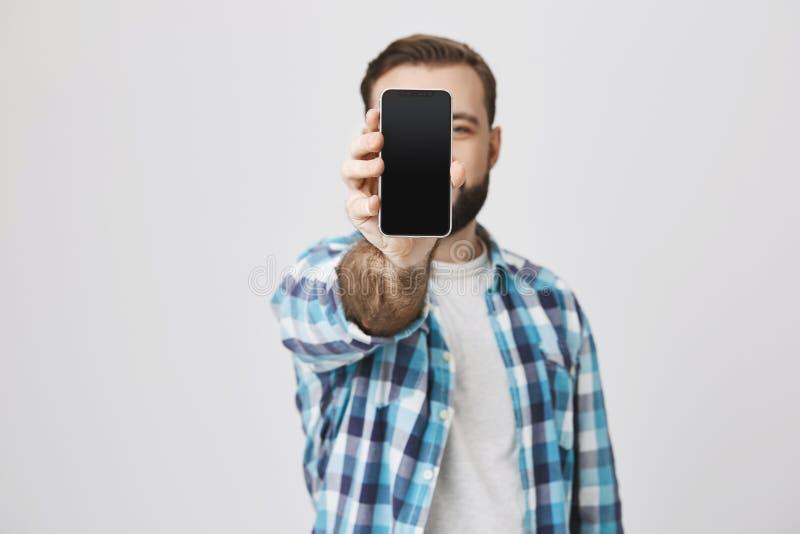 与胡子的男性模型和时髦理发在控制中显示智能手机的衬衣在照相机与它的覆盖物面孔,站立 免版税库存照片